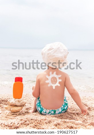 The sun drawing sunscreen (suntan lotion) on baby (boy)  back. Caucasian child is sitting with plastic container of sunscreen on beach. Copyspace. Close up, outdoor (Sharm El Sheikh, Egypt).  - stock photo