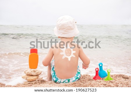 The sun drawing sunscreen (suntan lotion) on baby (boy)  back. Caucasian child is sitting with plastic container of sunscreen and toys on beach. Close up, outdoor, copyspace (Sharm El Sheikh, Egypt).  - stock photo