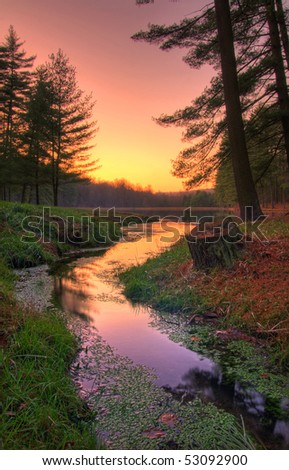 The sun goes down at the end of the day on a remote forest lake. - stock photo