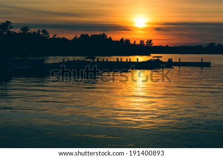 The sun is setting over a lake with boats docked on the water.  Silhouetted trees are seen against the orange sky.  Processed and toned for a vintage faded retro look.  - stock photo
