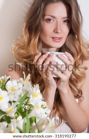 The sun is shining into the bedroom,she looks out the window.Hand and cup.The lady sitting beside the bed,her hand near her head,she looks into the camera.Morning with a cup in female hands - stock photo