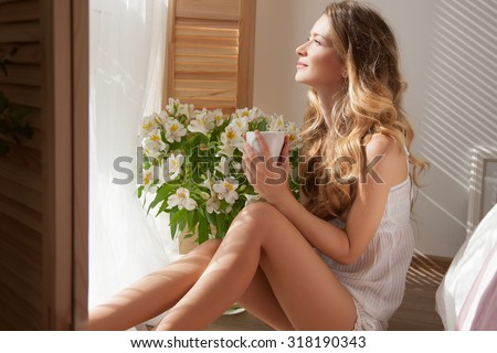 The sun is shining into the bedroom, she looks out the window. The lady sitting beside the bed, her hand near her head, she looks into the camera.Woman and flowers.Morning coffee, she closed her eyes - stock photo