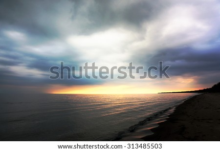 The sun on the horizon with storm clouds overhead of the shore of lake Erie.  Shot in Long Point Provincial Park, Ontario, Canada.  - stock photo