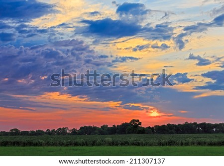 The sun rises behind clouds over Indiana farmland with trees silhouetted on the horizon. - stock photo
