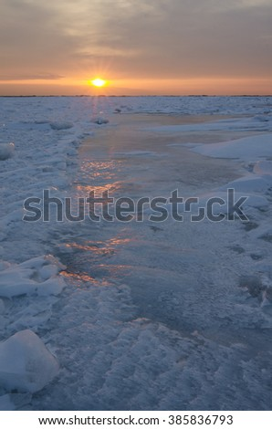 The sun rises over Lake Michigan and reflects red highlights on the ice, from Cana Island in Door County, Wisconsin - stock photo