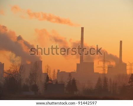 the sun rises over the coal power plant - stock photo