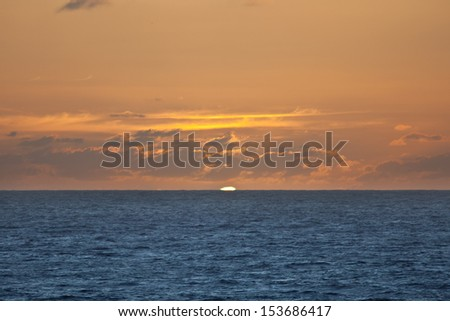 The sun rises over the South Pacific Ocean somewhere in French Polynesia. - stock photo
