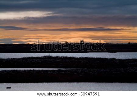 the sun rises over the tundra, churchill, canada - stock photo