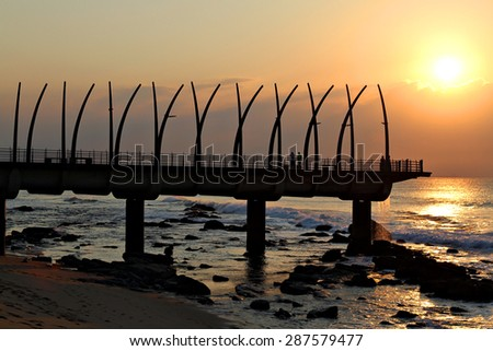 The sun rises over the Umhlanga Pier in Durban, South Africa. - stock photo