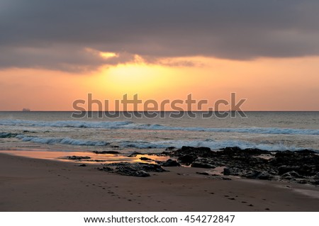 The sun rising into a bank of cloud, with rocks and beach in the foreground and ships on the horizon. - stock photo