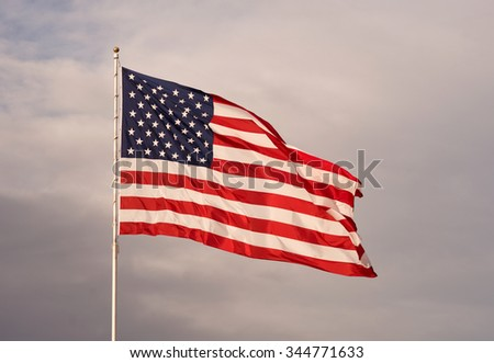 The sun sets and makes this flag glow on the way down - stock photo