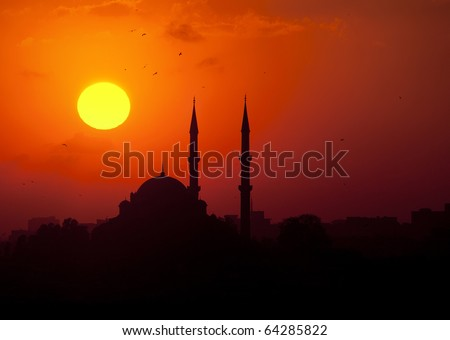 The sun sets behind a silhouetted mosque in Istanbul, Turkey - stock photo