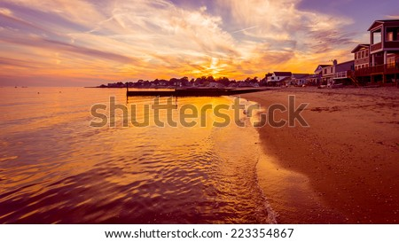 The sun sets on the final days of summer over a beach on Long Island Sound in Connecticut. - stock photo