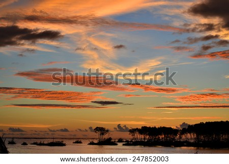 The sun sets over a lake. - stock photo