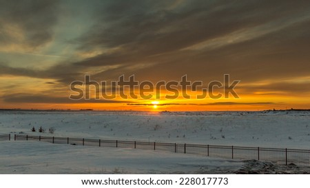 The sun setting on the vast snow covered flat lands of Saskatchewan Province in Canada. - stock photo