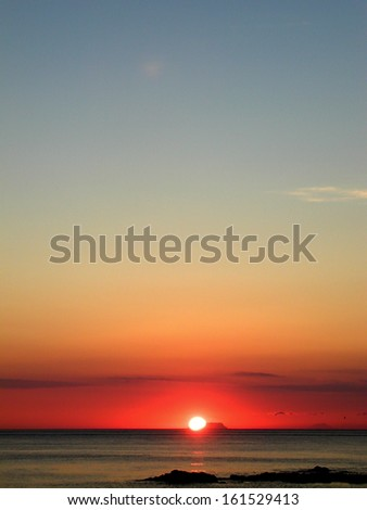 The sun setting over calm water. - stock photo