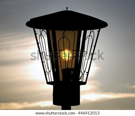 The sun shines through a street lamp. Photographed very close-up. In focus only lantern - stock photo