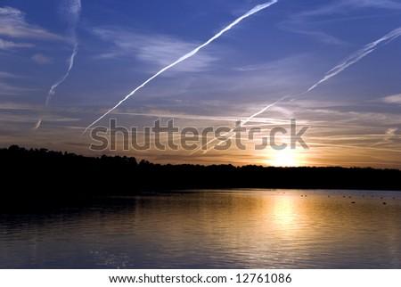 The sun shining on horizon behind clouds - stock photo