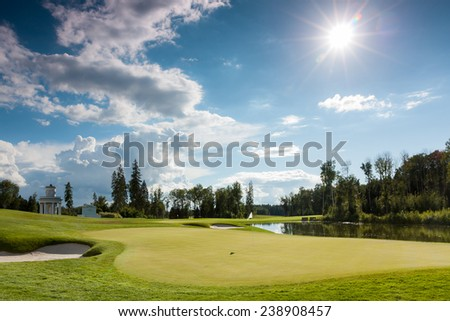 The sun shining over a golf course lined with buildings and trees - stock photo