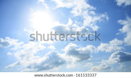 The sun shining through clouds in the sky. - stock photo
