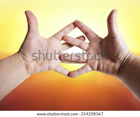 The sun through fingers of hands. - stock photo