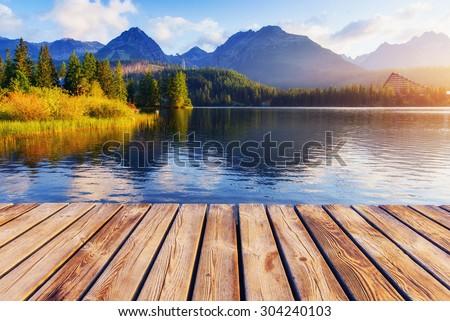 The sunrise over a lake in the park High Tatras. Shtrbske Pleso, Slovakia, Europe. - stock photo
