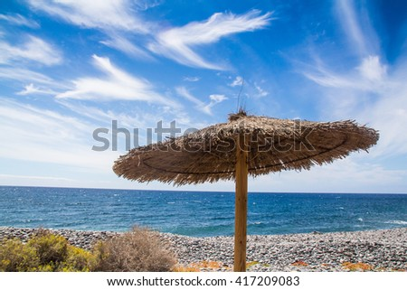 The Sunshade Umbrellas At The Beach in the blue sky and sandy beach background - stock photo