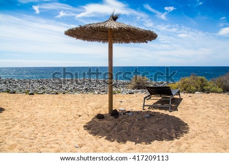 The Sunshade Umbrellas At The Beach in the blue sky and sandy beach background.  - stock photo