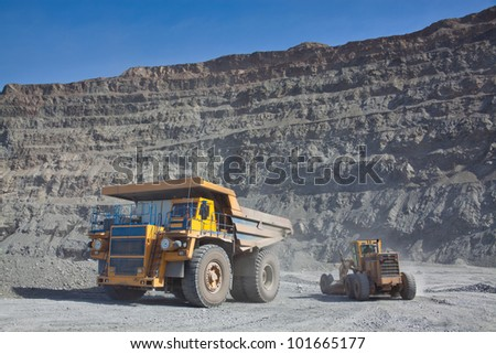 The supersize car and grader in open pit mine - stock photo