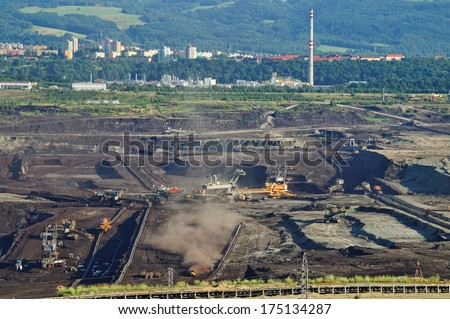 The surface mine mining of brown coal, in the bottom of the pit mining machinery, in the background chemical factory the city and the forest, view from above - stock photo
