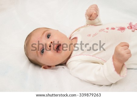 The surprised baby girl lying on white towel  - stock photo
