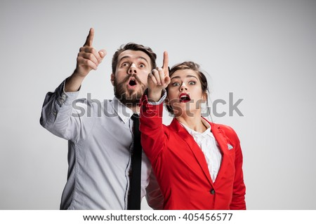 The surprised business man and woman showing up on a gray background - stock photo