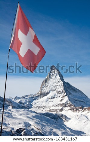 The Swiss flag infront of the Matterhorn - stock photo
