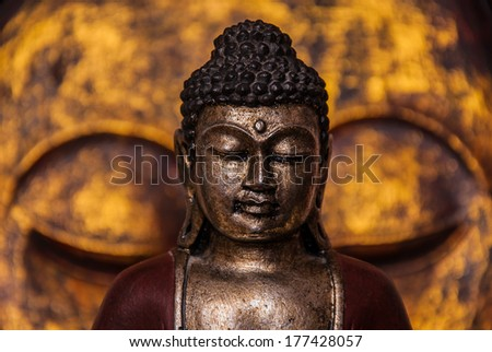 The symbol of the richness, of the founder of Buddhism, Buddha miniature statue sculpture with golden painted wood carved Buddha face on the background, vivid colors - stock photo