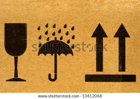 The symbols 'fragile', 'keep dry' and 'this way up' on cardboard. - stock photo