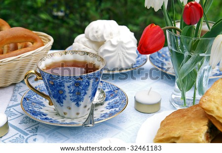 The table set for afternoon tea in a summer garden - blue tea-things, pastry, marshmallows, flowers in a vase, blur background - stock photo