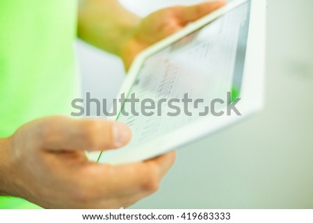 the tablet in his hands with the graph depicted on the screen - stock photo