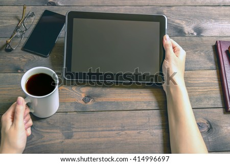 The  tablet  is in female hands. Dark brown wooden background. Diaries and cup of coffee. Modern devices. Blank display. Woman's hand with the device plate. - stock photo