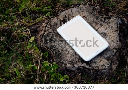 The tablet on wood stump - stock photo