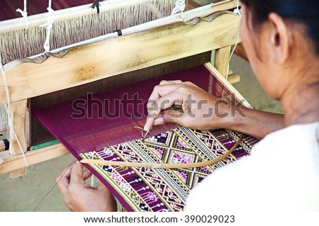 The Tai Puan people, local woman weaving the woven textiles, Teen Jok pattern in her home-use hand-woven at Ban Had Saew Village, Si Satchanalai District, Sukhothai, Thailand., selective focus - stock photo