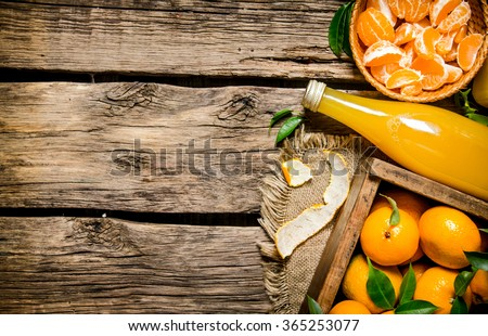 The tangerine background. Tangerines in a box, spooned into the Cup and the juice in the bottle. On wooden background.  Free space for text . Top view - stock photo