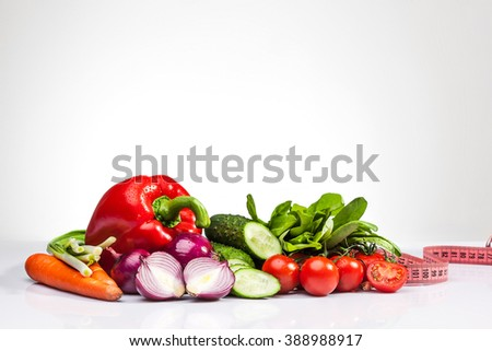 The tape measure with tomatoes and vegetables on white - stock photo