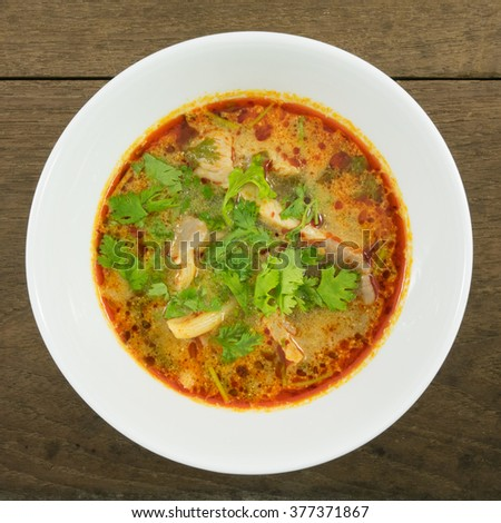 The tasty spicy pork tom yum soup (hot and sour soup) in white ceramic bowl, homemade Thai food. - stock photo