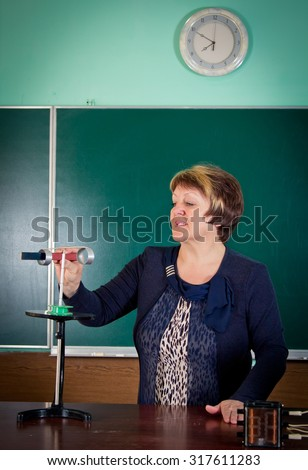 The teacher of physics explains concept of electromagnetic induction. Electrical engineering   bases - stock photo