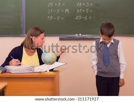 The teacher scolds a little schoolboy in a classroom. - stock photo
