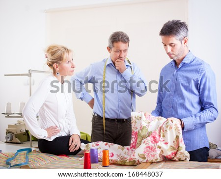 The team of tailors evaluated cloth in their workroom.  - stock photo