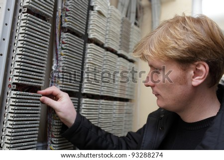 The technician touching terminal bloc on the telecom site - stock photo