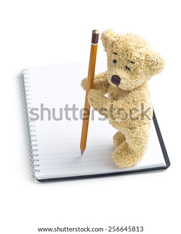 the teddy bear with pencil on blank notebook - stock photo