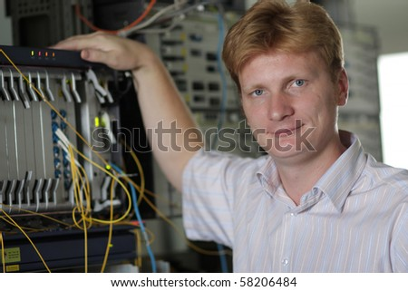 The telecom engineer poses on a multiplexer background - stock photo