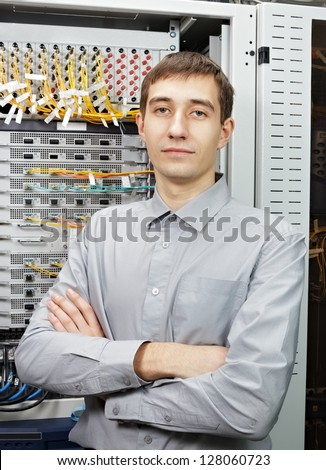 The telecom engineer stand in data center near telecommunication equipment. - stock photo